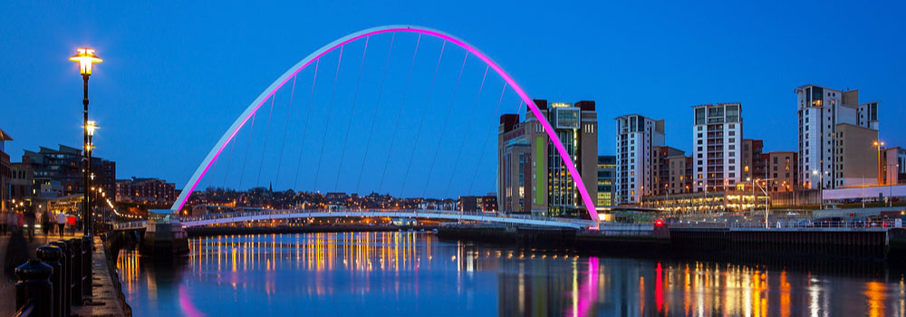 Gateshead Millennium Bridge at night with the bridge lit up