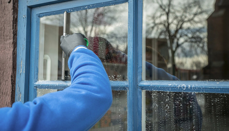 person cleaning window glass outside of a house
